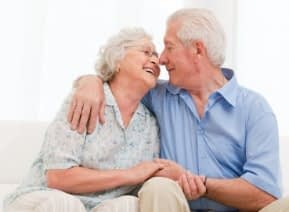 old couple smiling at each other, newlyweds