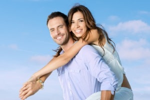 Smiling Young Man Piggybacking His Pretty Girlfriend - what do men really want in a woman