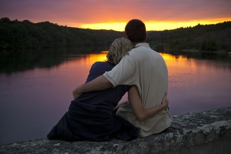 A couple gently embrace as the sun sets