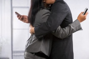 couple hug yet still using cell phone - How To Tell If Your Spouse is Cheating on You signs